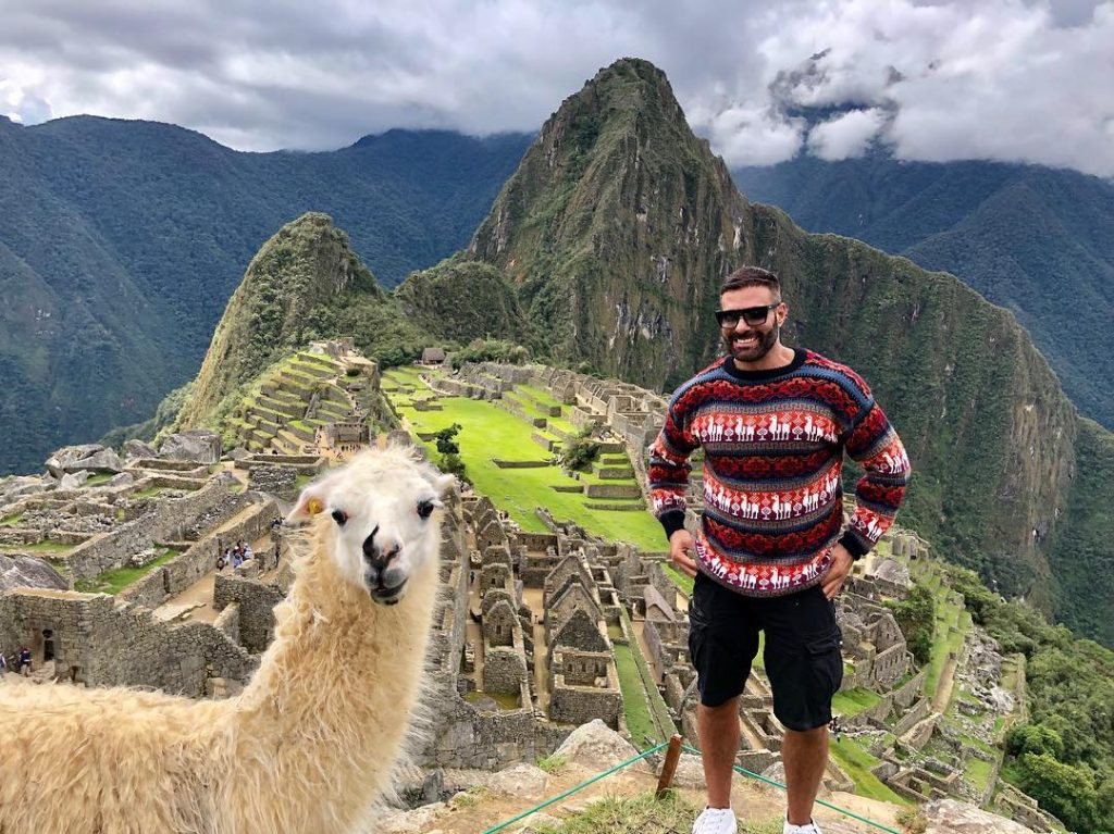 Person and llama in Machu Picchu