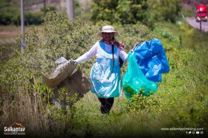Woman picking up garbage.