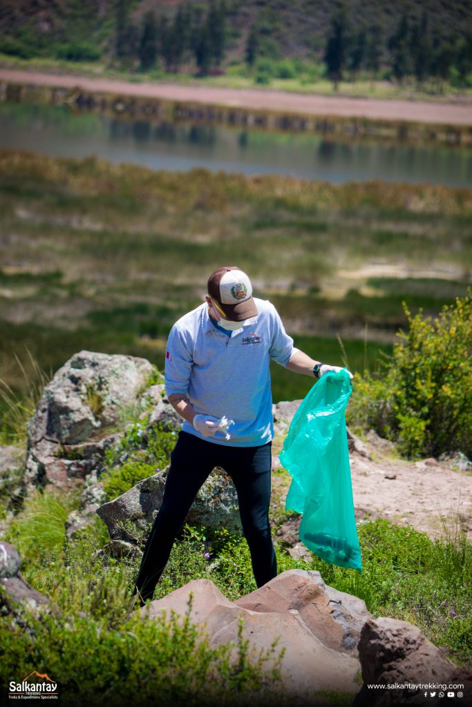 Man picking up trash next to Pikillaqta Huacarpay