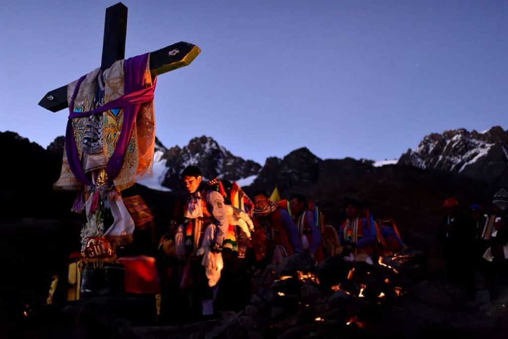 Andean cross and traditional dancer at the mountains